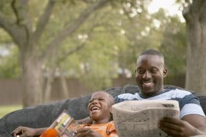 Father and son laughing and reading | Melissa Graham-Hurd & Associates