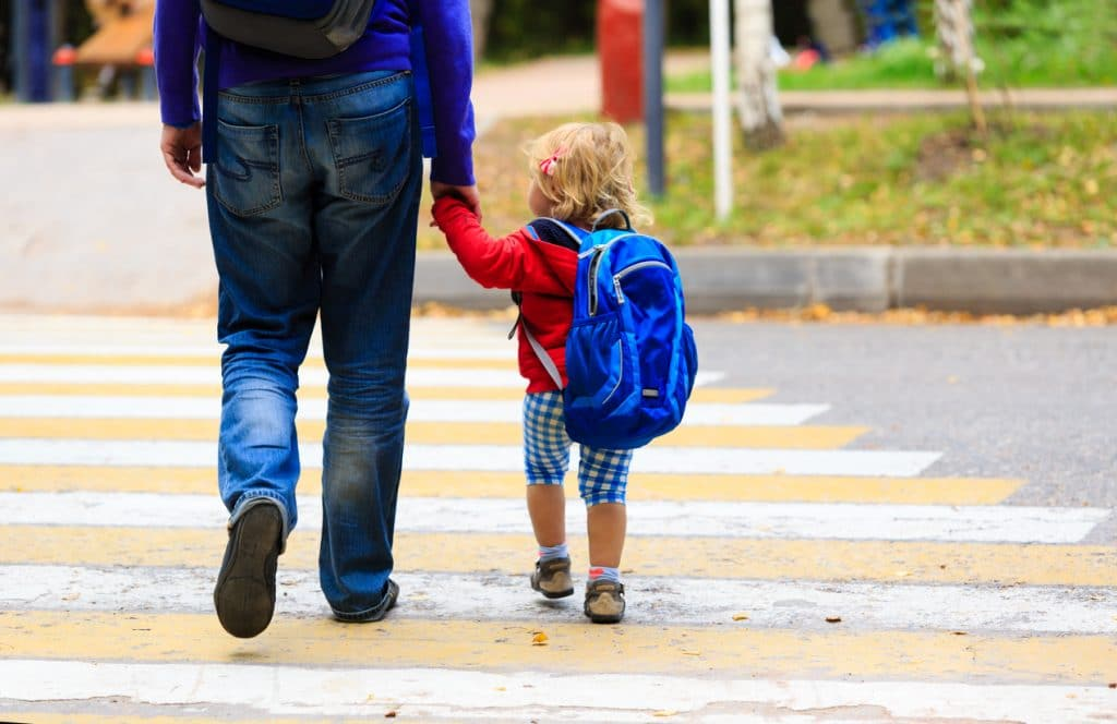 Father walking little daughter with backpack to school